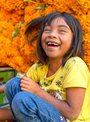 Laughing mexican children with a background of orange marigolds