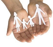 Childs hands holding paper doll family
