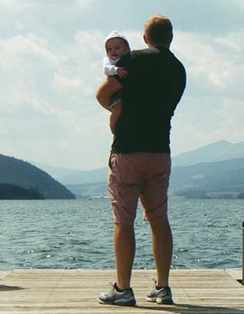 father holding child and looking across lake with mountains behind