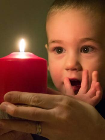 Toddler looking at a candle with wide eyes.