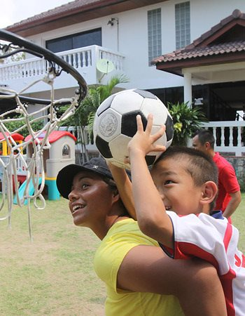 An older child lifting a younger one on her back so he can reach the rim of a basketball hoop and throw a soccer ball into it.