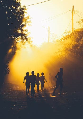 silhouettes of a group of children running on a forest path