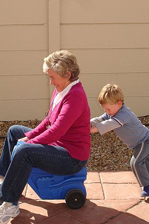 A small boy pushing his grandmother on a plastic play toy.