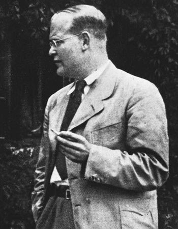 Dietrich Bonhoeffer, standing and smoking a pipe.