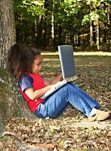 girl under a tree with a laptop