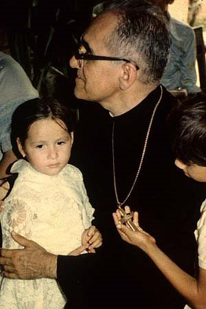Archbishop Oscar Romero with two children, one of whom is holding his archbishop's cross in his hand and gazing at it.