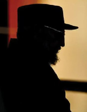Fidel Castro's head and shoulders in silhouette against a mustard-colored wall.