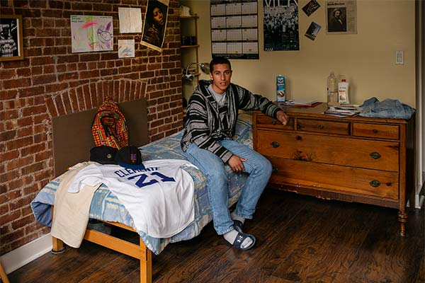 Rubén Ayala sitting on a bed surrounded by mementos of his dad
