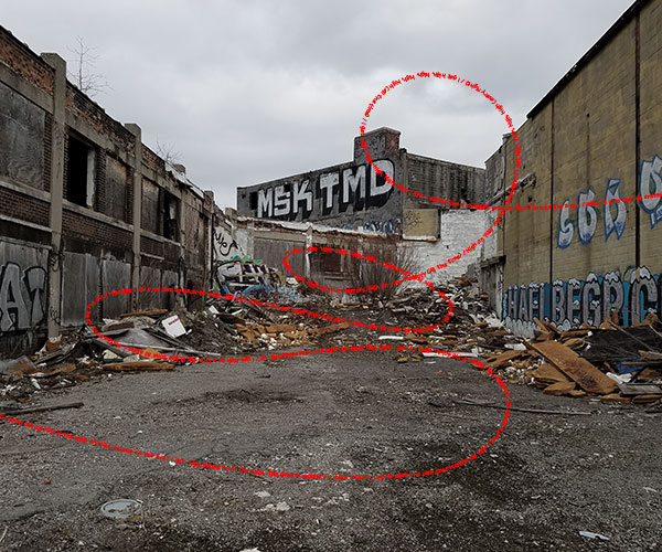 photo of a rubble filled alley with red text of a rap song overlaid